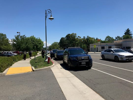 Redding police cars are parked near Redding Library, where a man was shot on Monday, June 3, 2019.