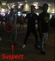 This photo released by Rehoboth Beach Police Department shows the suspect putting the knife back in his right pants pocket.  It also shows two of the accomplices, a black male wearing a black T-shirt, black pants, and white shoes and a black male wearing a black Polo T-shirt, blue jeans, and black shoes.