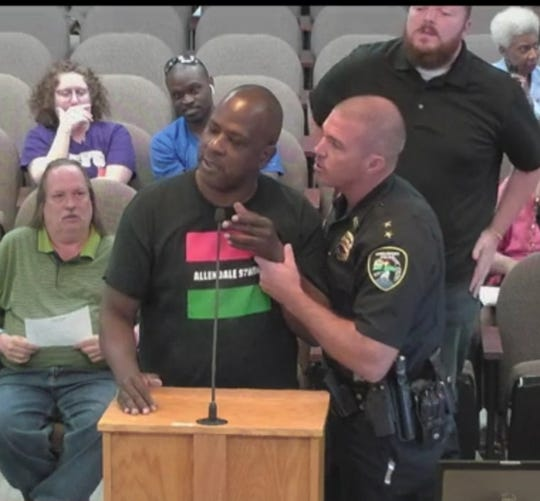 Police Chief Ben Raymond attempting to remove activist Marvin Muhammad from a City Council meeting.