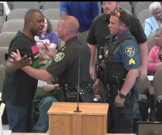 Marvin Muhammad reacted aggressively when Police Chief Ben Raymond attempted to remove him from the room during public comment. Activists complained Raymond should not have put his hands on Muhammad during the process.