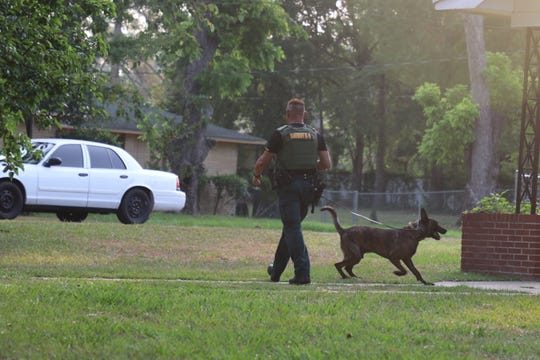 "A Leon County Sheriff's Office deputy and K9 ""Tater"" move toward a suspect's house"