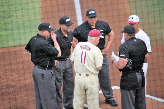 FSU coach Mike Martin meets with the umpires before FSU's Athen's Regional Championship Game against Georgia.