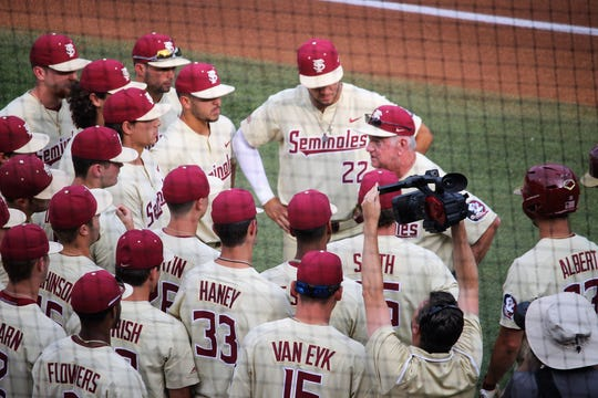 FSU coach Mike Martin meets with his team before FSU's Athen's Regional Championship Game against Georgia.