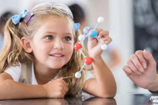 An elementary schoolgirl analyzes a model of the molecular structure.