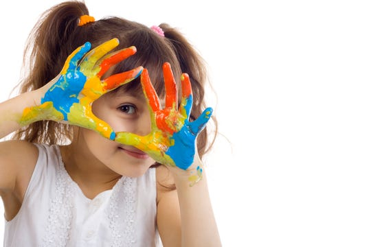 A young girl playing with colors