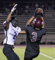 Mt. Whitney's Anthony Valencia takes a pass under pressure from Mission Oak's Davin Campbell in a non-league high school football game on Friday, September 7, 2018.
