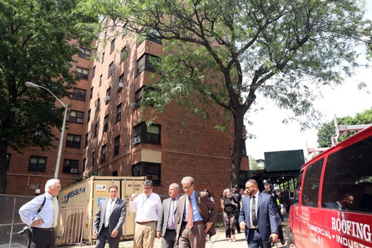 Municipal Housing Authority for the City of Yonkers Executive Director Joseph Shuldiner, center, gives Mayor Mike Spano and Police Commissioner Charles Gardner, second left, a tour of the William A. Schlobohm Houses, a public housing complex in Yonkers, with Deputy Executive Director Carlos Laboy-Diaz May 31, 2019.