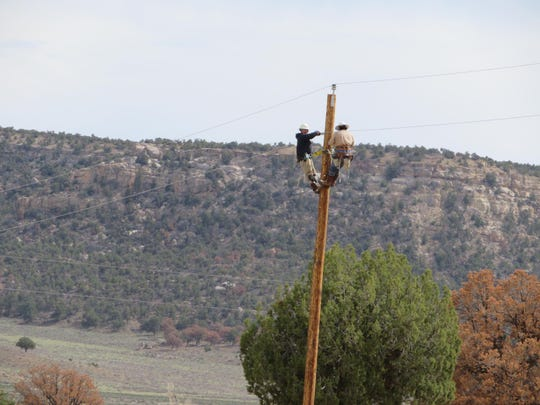 Delaware Municipal Electric Corporation workers install utility poles as part of a project to bring electricity to a remote Navajo Nation town.