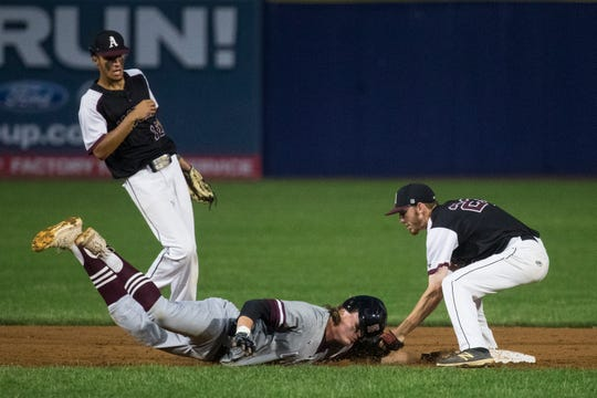 Appoquinimink's Trevor Coleman (23) tags out Caravel's Cole Reynolds (15) as he dives back to second base in the DIAA Baseball Championship at Frawley Stadium.