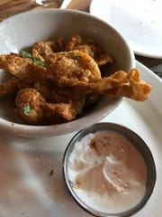 "Chicken skins  with ranch dressing are a popular dish at Farmer & The Cow in Wilmington. The $9 dish was featured on the Food Network series ""Diners, Drive-ins and Dives."""