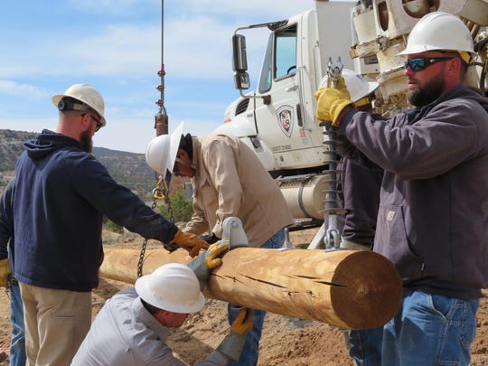 Delaware Municipal Electric Corporation workers install utility pole as part of a project to bring electricity to a remote Navajo Nation town.