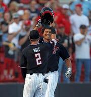 Texas Tech's Cameron Warren (right) high-fives Gabe Holt (2) after hitting a three-run home run Sunday.