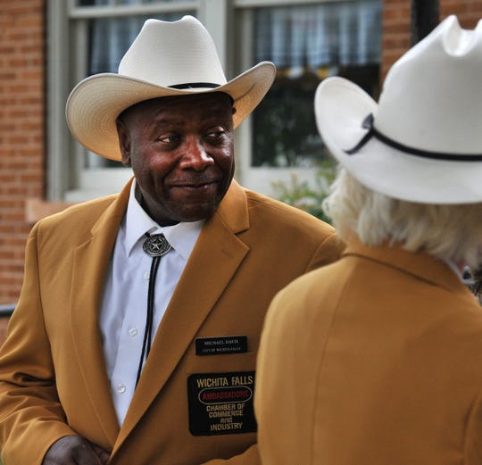 Gold Coat Ambassador Michael Davis chats with fellow ambassadors after attending a ceremony Monday.