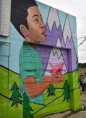 A hillside, children, origami and mountains were all part of the design that artist Selena Mize created for the mural at the corner of Harding and Rosewood.