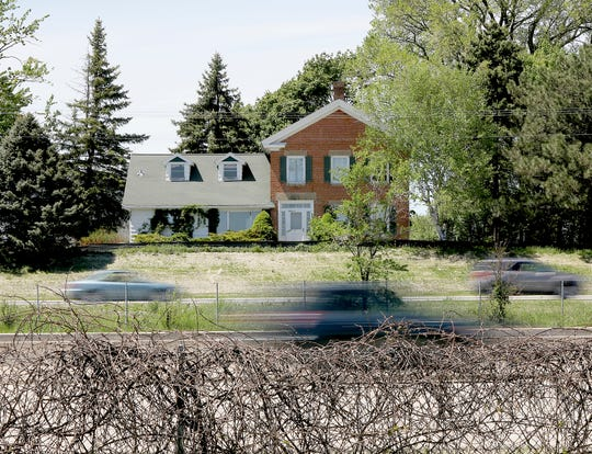 In a Thursday, May 23, 2019 photo, traffic on Highway 151 moves past the former Thompson-Schneider farmstead in Sun Prairie, Wis. History is now catching up with the home, which is slated to be burned in a series of training exercises by the city's fire department.