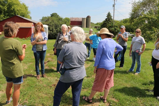Kirsten Jurcek  (left) of Brattset Family Farm shared conservation practices on the farm at a 2016 farm tour. Jurcek will host a June 18th twilight pasture walk focused on grazing's impact on groundwater.