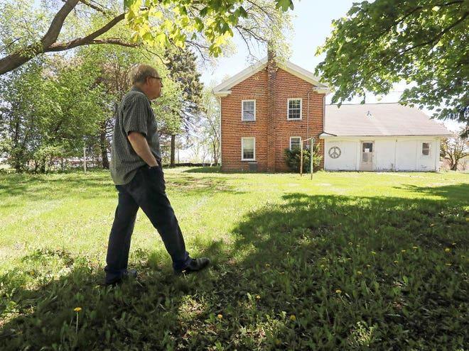 In a Thursday, May 23, 2019 photo, former Sun Prairie Mayor Joe Chase walks the grounds of a Civil War-era home and farmstead on the west side of the city. History is now catching up with the home, which is slated to be burned in a series of training exercises by the city's fire department.