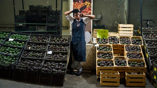 FILE - In this Aug. 9, 2016 file photo, an avocado vendor talks on his cellphone at a market in Mexico City.  Summary: The potential Trump tariffs are expected to hit U.S. avocado lovers more than Mexican producers.