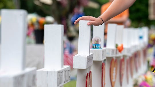 People pay their respects on June 2, 2019, at a memorial for the victims of a mass shooting that killed twelve in Virginia Beach, Va.