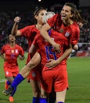 Tobin Heath celebrates a goal with teammates Megan Rapinoe (15) and Alex Morgan.