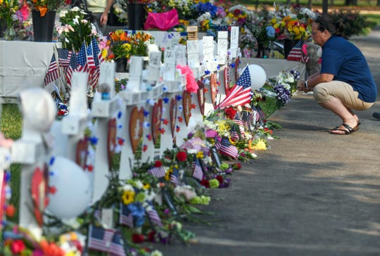 People stop by a memorial to victims of a mass shooting on June 3, 2019, in Virginia Beach.