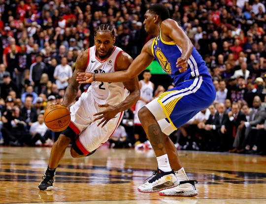 Raptors forward Kawhi Leonard drives to the basket against Warriors center Kevon Looney during Game 1 of the NBA Finals in Toronto.