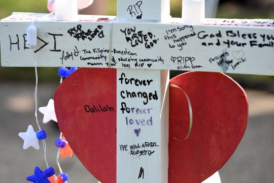 People leave handwritten messages at a memorial to victims of a mass shooting that killed 12 in Virginia Beach, Va.