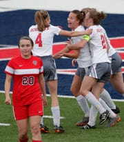 Neenah's Maria Sorensen, center, is mobbed by teammates after scoring a goal against Appleton East during their girls soccer game May 28 in Appleton.