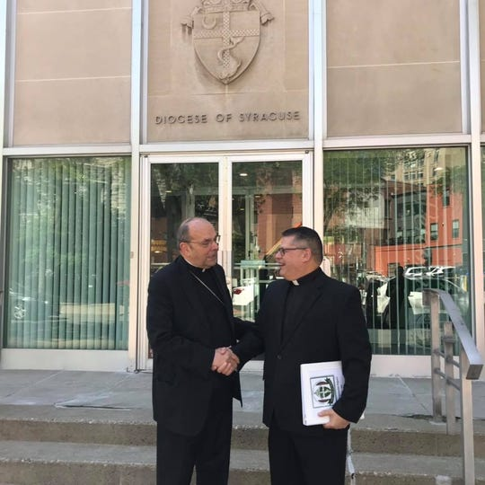 Bishop Cunningham presents the Quinquennial report to Bishop-elect Lucia outside the Chancery in Syracuse.