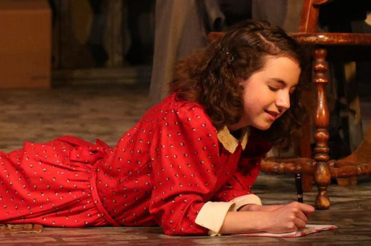 Anne Frank (Madilyne Nelsen) makes an entry in her diary.