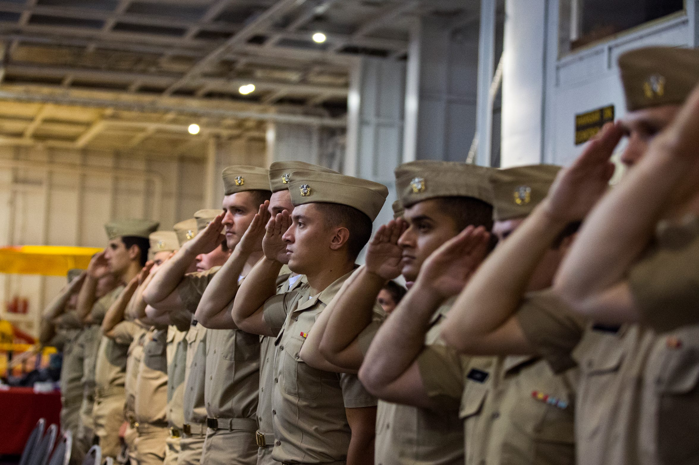 Military personnel salute during the National Anthem at the the Commemoration of the Battle of Midway and of D-Day at the USS Lexington Museum on the Bay in Corpus Christi.