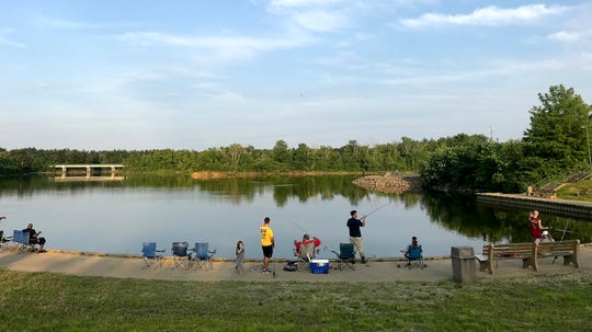 Despite signs warning that Winton Woods Lake was closed because of sewage overflowing from a manhole north of it, people were still fishing in the lake.