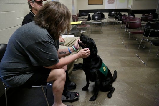 Kelly Phipps, who graduated from the inpatient program and is training to be a peer mentor, pets Frye, a trained member of Therapy Pets of Greater Cincinnati as he visits the Center for Addiction Treatment in the West End neighborhood of Cincinnati on Sunday, June 2, 2019.