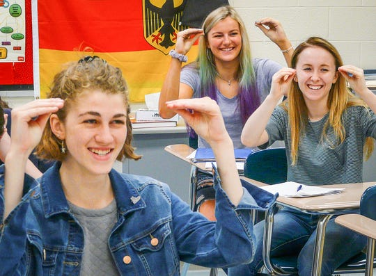 "Showing the sign for ""teach,"" are (from left) Julianna Hinrichsen, Kadie McNally and Morgan Middleberg, students finishing their first year of entry-level American Sign Language."