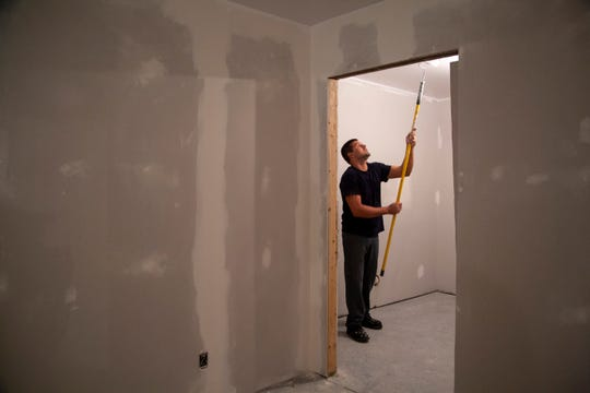 Newton Correctional Facility inmate Joshua Goemaat of Knoxville works May 28 to paint a room inside an old barn that is being converted as part of a new Iowa Prison Industries program. Inmates will build homes for communities in need.