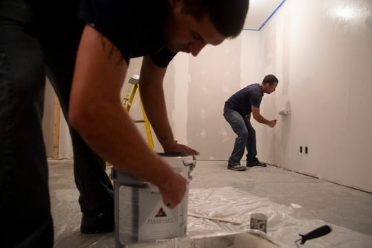 Newton Correctional Facility inmates Daniel Garcia, right, of Council Bluffs and Joshua Goemaat, left, of Knoxville work on painting a room inside an old barn that is being converted as part of Iowa Prison Industries' new program in which inmates build homes for communities in need.