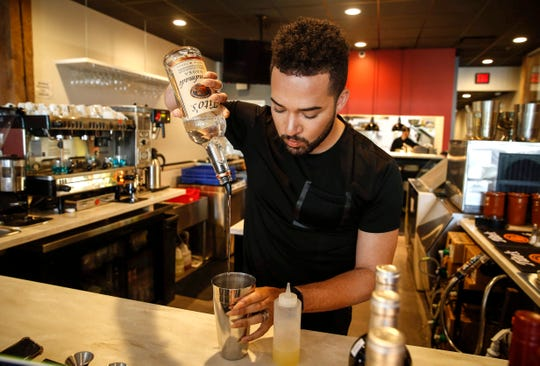 DiAndre Neville prepares a cocktail at Bistro Nomad in Des Moines.