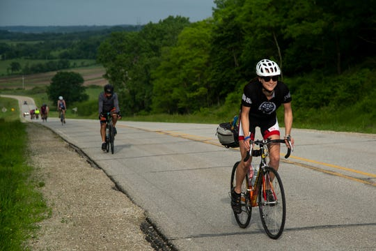 RAGBRAI's Andrea Parrott tops a hill as riders on RAGBRAI's Pre-Ride make their way from Winterset through The Ag Oasis and onto the day three end town of Indianola on Tuesday, June 4, 2019.