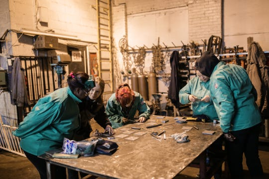 Women Who Weld founder and instructor Samantha Farr helps Dedria House (left) of Detroit measure to drill holes on a steel plate at the Addison Iron Fabricators in Detroit on Thursday, March 31, 2016.