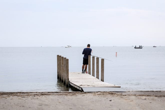 A young man fishes on a pier near the boat launch at Lake St. Clair Metropark in Harrison Twp., Mich. on Saturday, June 9, 2018.