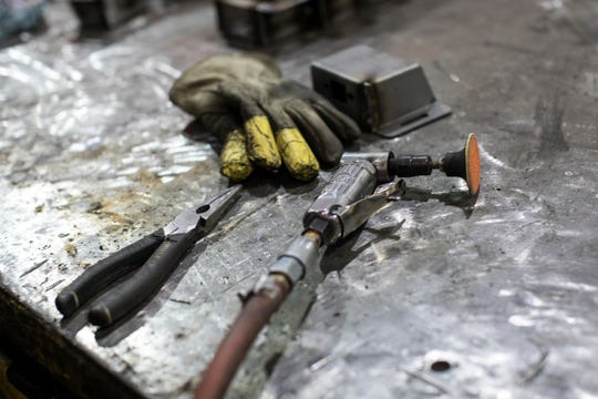 Pliers, gloves and a grinder rest on the worktable Fredrea Lakes, 29, of Oak Park uses for tack welding sub-assembly at the Armored Group in Dearborn Heights on Monday, June 3, 2019.
