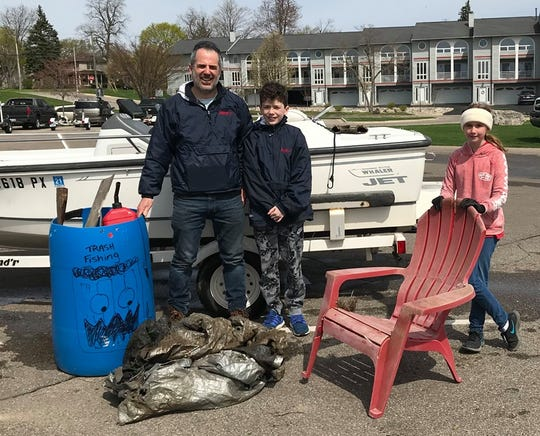 Tom Nardone, left, with a load of trash he found while trash fishing.