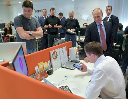 In this Thursday, Sept. 21, 2017 file photo, Russian President Vladimir Putin, right, visits Russia's largest internet search engine Yandex headquarters in Moscow, Russia.