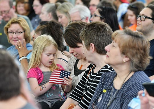 Emilie MacAulay, center, of Ferndale sits with her daughter, Corinne, 4, and her mother, Susan Oswald, right, before the start of the Detroit Community Conversation with Elizabeth Warren at Focus: HOPE in Detroit on June 4, 2019.