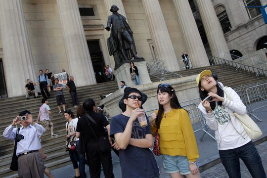 A group of tourists from China take in the sights of the New York Stock Exchange and Federal Hall National Memorial in 2012. China has issued a travel warning for the U.S. saying Chinese visitors have been interrogated, interviewed and subjected to other forms of what it called harassment by U.S. law enforcement agencies.