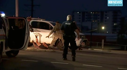 In this image made from video, police  apprehend a suspect on the ground next to a white truck, Tuesday, June 4, 2019, in Darwin Australia.