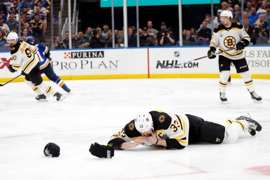 Bruins defenseman Zdeno Chara (33) lies on the ice after getting hit in the face with the puck during the second period of Game 4 on Monday.