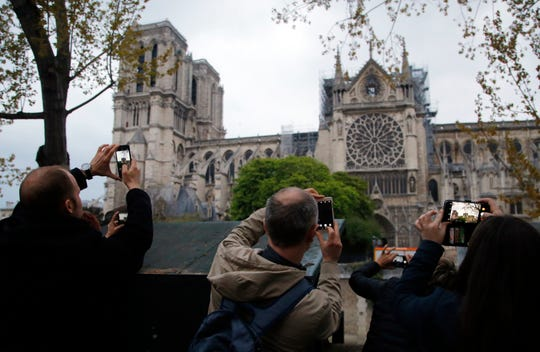 People take photos of the Notre Dame Cathedral in Paris in April, one day after a major blaze broke out at Paris' iconic cathedral. Children under 7 and pregnant women who live near Notre Dame Cathedral may have been exposed to lead pollution in the area.