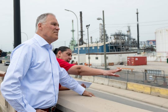 Theresa Landrum, a member of the 48217 community monitoring group, points out features of the Marathon refinery in southwest Detroit to Washington Governor and democratic presidential candidate Jay Inslee during a tour of the neighborhood.