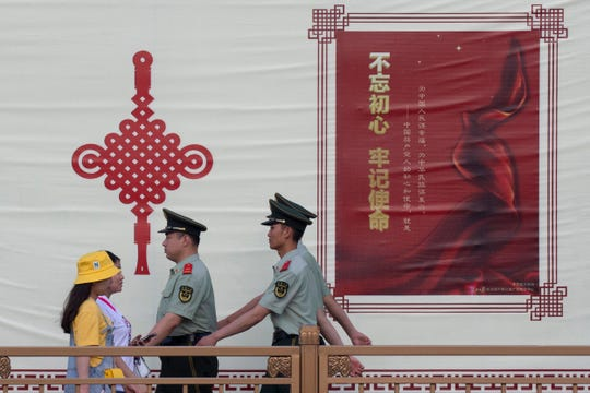 "Paramilitary policemen march past a government propaganda banner with the words ""Never forget our original aspirations, Keep our mission firmly in mind"" along a street leading to Tiananmen Square in Beijing on Friday."